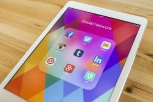 All of popular social media icons on Apple new iPad Air device screen wood background, social media to attract talent.