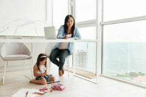 Work life balance, young woman write notes while her little daughter at home indoors sitting on floor.