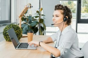 Woman at computer with headphones, podcast analytics, podcast.
