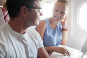 Happy young people traveling by plane. Woman talking to a man while using laptop. Bright sunlight in airplane windows