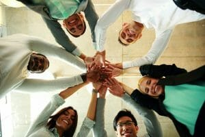 business people teamwork in an office with hands together, healthy employee engagement