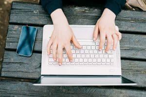Top view of the hands of a woman tapping the keyboard of a laptop, creating product page