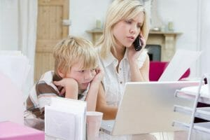 Woman using telephone in home office with laptop while young boy, life balance