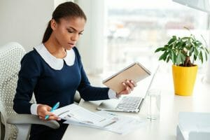 African business woman in dress working with laptop and documents on workplace near the window, selling a business