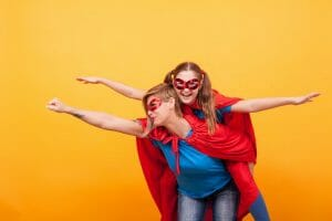 Beautiful mother and her cute little girl playing together dressed like superheros over yellow background.